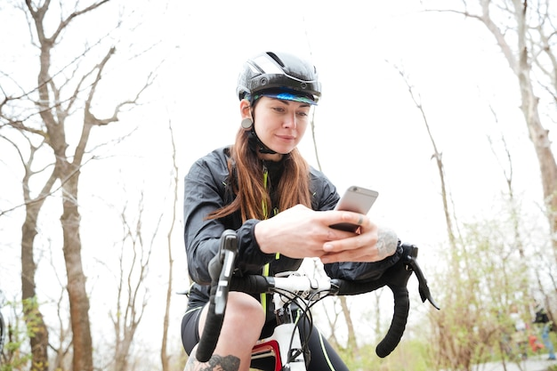 Piękna kobieta na rowerze za pomocą smartfona