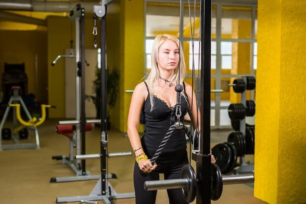 Piękna kobieta na siłowni, ćwiczenia na maszynie.
