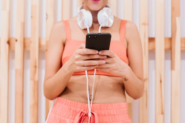 Piękna kobieta na siłowni przy użyciu telefonu komórkowego i uśmiechnięty