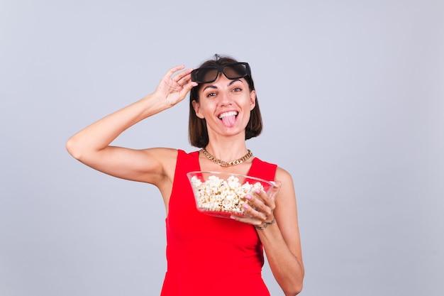 Piękna kobieta na szarej ścianie w okularach kinowych 3d z popcornem, wesołe szczęśliwe pozytywne emocje
