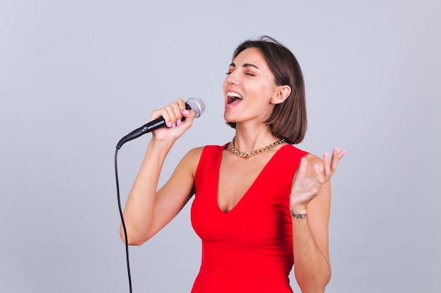 Piękna kobieta na szarej ścianie z mikrofonem śpiewa emocjonalną ulubioną piosenkę szczęśliwą pozytywną wesołą