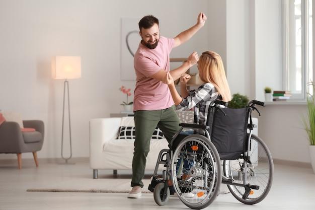 Piękna kobieta na wózku inwalidzkim z mężczyzną tańczy w domu