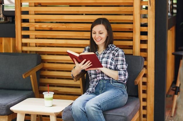 Piękna kobieta na zewnątrz ulicy letnia kawiarnia drewniana kawiarnia siedząca w swobodnych ubraniach, czytająca książkę z filiżanką koktajlu