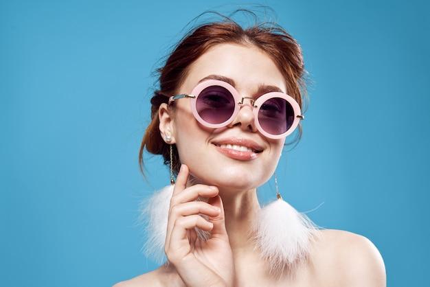 Piękna kobieta nagie ramiona puszyste kolczyki okulary przeciwsłoneczne akcesoria makijaż. wysokiej jakości zdjęcie