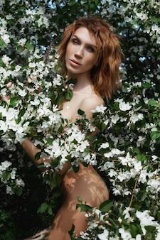 Piękna kobieta nago sztuki w gałęziach i liści kwitnącej jabłoni w przyrodzie. piękne szczupłe ciało, naturalne kosmetyki i uroda. kwiaty jabłoni na ciele dziewczyny