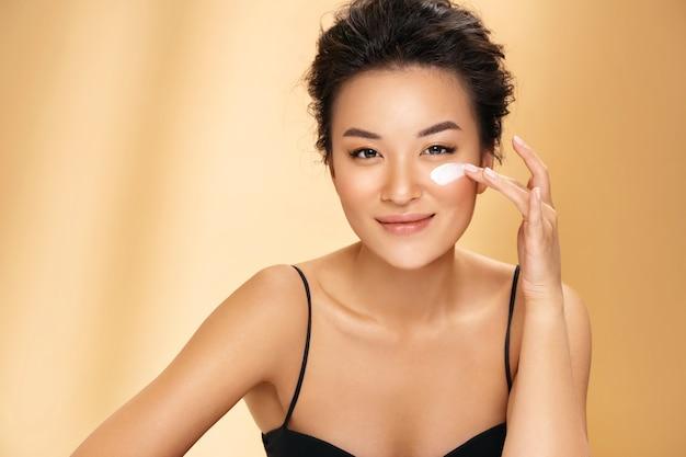 Piękna kobieta nakłada krem nawilżający na twarz