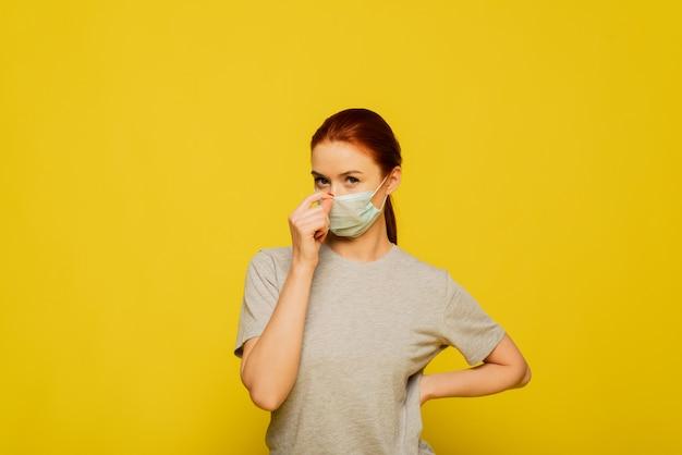 Piękna kobieta nakłada medyczną maskę na żółtej ścianie. koncepcja koronawirusa i covid-19.