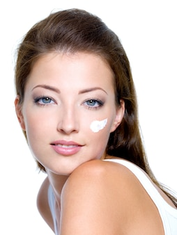 Piękna kobieta nakłada nawilżający krem kosmetyczny na twarz - na białym