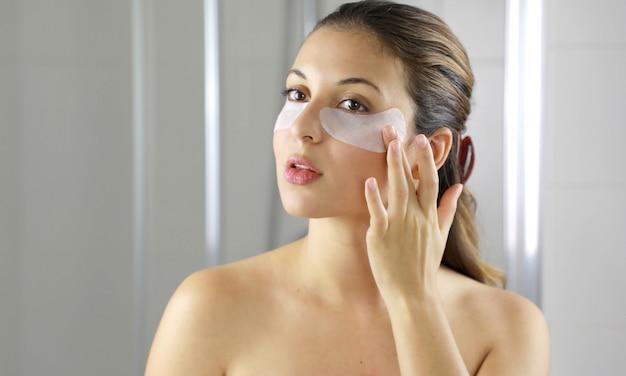 Piękna kobieta nakładająca przeciwstarzeniową maseczkę pod oczy, patrząc w lustro w łazience.