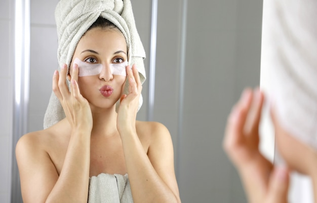 Piękna kobieta nakładająca przeciwzmęczeniową maseczkę pod oczy całuje się w lustrze w łazience.