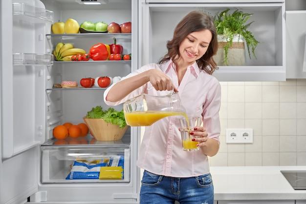Piękna kobieta nalewa świeżego sok pomarańczowy w szkle
