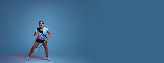 Piękna kobieta niepełnosprawna uprawiająca badmintona na białym tle na niebieskim tle w świetle neonu. styl życia ludzi włączających, różnorodność i równość. sport, aktywność i ruch. copyspace dla reklamy. ulotka