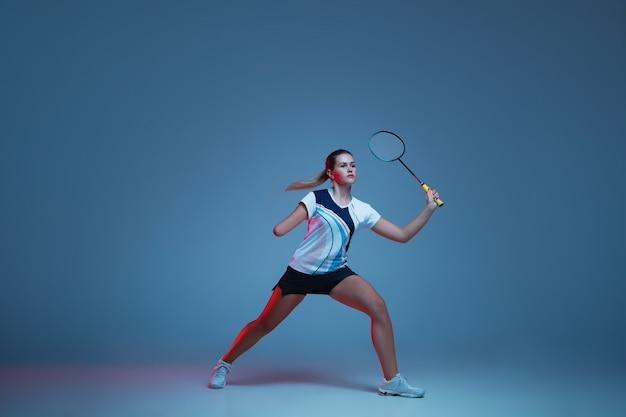 Piękna kobieta niepełnosprawna uprawiająca badmintona na białym tle na niebieskim tle w świetle neonu. styl życia ludzi włączających, różnorodność i równość. sport, aktywność i ruch. copyspace dla reklamy.