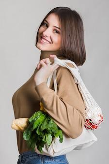 Piękna kobieta niesie organicznie warzywa