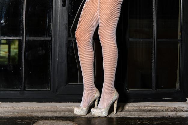 Piękna kobieta nogi w białych pończochach na wysokich obcasach stojąc na parapecie