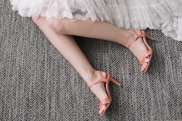 Piękna kobieta nogi w wysokich obcasach. suknia ślubna i buty. poranek panny młodej