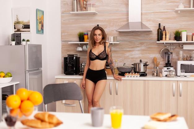 Piękna kobieta nosi bieliznę w domowej kuchni podczas śniadania. młoda seksowna uwodzicielska dama z tatuażami pijąca zdrowy, naturalny domowy sok pomarańczowy, orzeźwiający niedzielny poranek