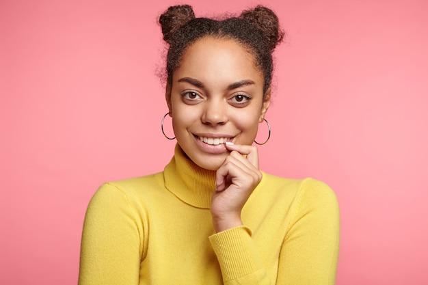 Piękna kobieta nosi kolczyki i żółty sweter