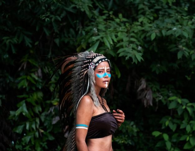 Piękna kobieta nosi nakrycia głowy z piór ptaków. maluje ciało w kolorze brązowym i twarz w kolorze niebieskim, model pozuje w lesie