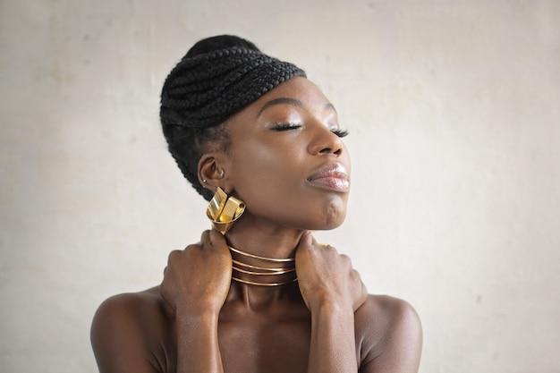 Piękna kobieta nosi złote kolczyki i naszyjnik