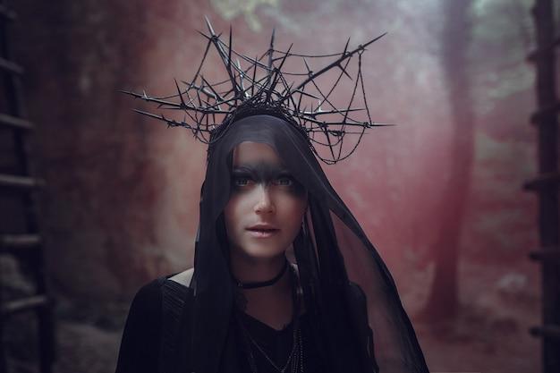 Piękna kobieta o bladej skórze w czarnej sukni i czarnej koronie. gotycki wygląd. strój na halloween. kobieta z kolorowym dymem