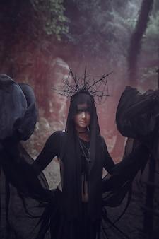 Piękna kobieta o bladej skórze w czarnej sukni i czarnej koronie. gotycki wygląd. strój na halloween.