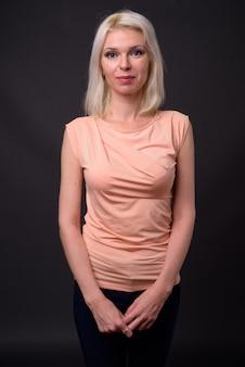 Piękna kobieta o blond włosach na szarym tle