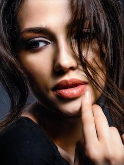Piękna kobieta o brązowych włosach. atrakcyjny model o brązowych oczach. modelka z smokey makijaż. zbliżenie portret ładnej kobiety patrzy na aparat.