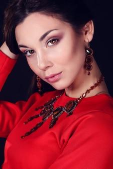 Piękna kobieta o ciemnych włosach i wieczorowy makijaż. biżuteria i piękno. fotografia mody
