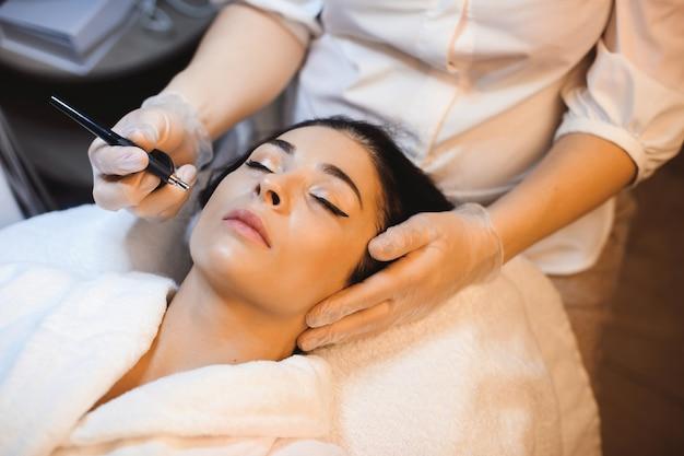 Piękna kobieta o czarnych włosach ma zabieg przeciw trądzikowi w salonie spa
