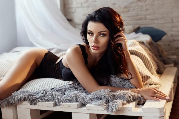 Piękna kobieta o długich czarnych włosach siedzi na łóżku w czarnej bieliźnie.