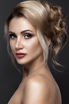 Piękna kobieta o doskonałej skórze, wieczorowym makijażu, fryzurze ślubnej