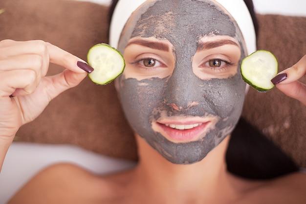 Piękna kobieta o glinianej maseczce na twarz nakładana przez kosmetyczkę.
