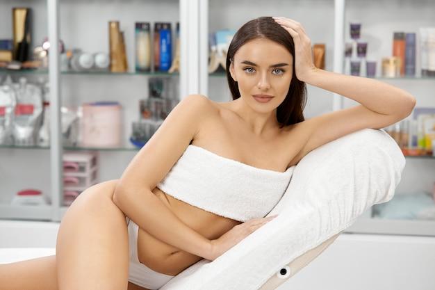 Piękna kobieta o idealnym ciele siedzi w spa w białych spodniach i biuście przykrytym ręcznikiem