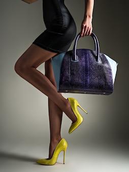 Piękna kobieta o szczupłych nogach w żółtych szpilkach. modna dziewczyna trzyma stylową niebieską torbę. stylowa koncepcja glamour. sztuka. kobieta idzie po zakupach. nie do poznania kobieta.