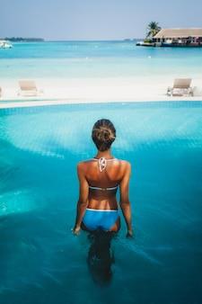 Piękna kobieta o szczupłym ciele do opalania i relaksu w basenie ośrodka