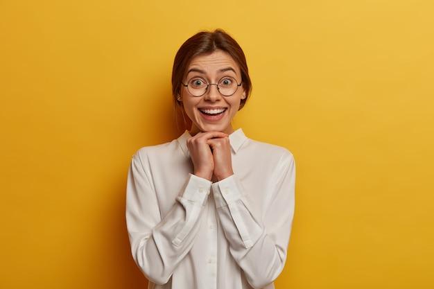 Piękna kobieta o wesołym wyrazie, trzyma ręce pod brodą, nosi schludną białą koszulę i duże okrągłe okulary, wygląda radośnie, jest w dobrym nastroju, odizolowana od żółtej ściany.