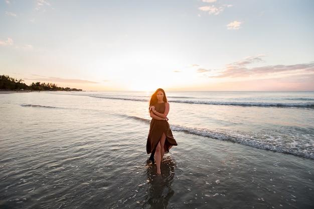 Piękna kobieta o zachodzie słońca. kolorowy świt nad morzem. beztroska kobieta cieszy się zmierzch na plaży. szczęśliwy styl życia