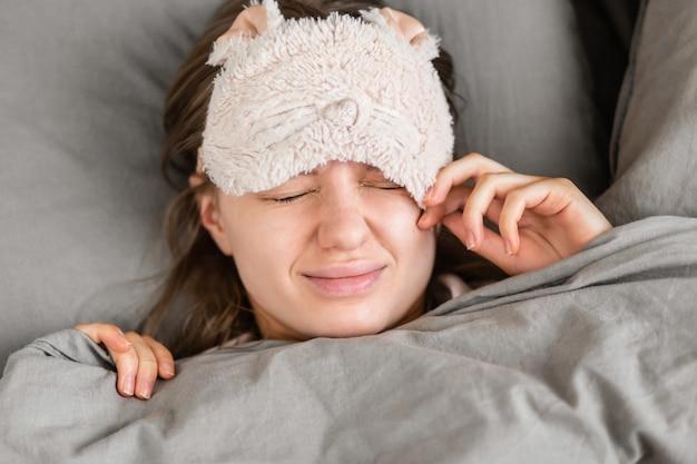 Piękna kobieta obudziła się w domu w łóżku i zdjęła maskę do spania z twarzy. dzień dobry. zdrowy sen.
