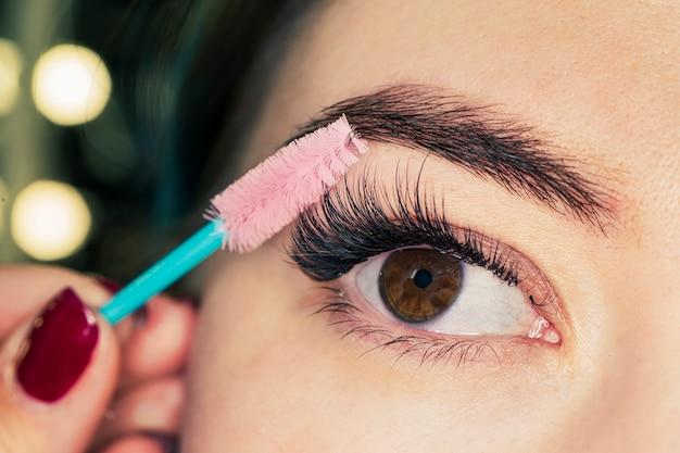 Piękna kobieta oczy makijaż. nakładanie tuszu do rzęs. zbliżenie długie rzęsy. pędzel do tuszu do rzęs. przedłużanie rzęs. makijaż dla czarnych oczu. nakładanie makijażu oczu, modelowanie brwi.