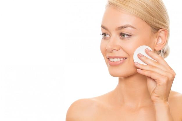 Piękna kobieta oczyszcza jej skórę