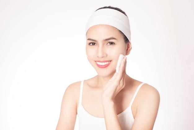 Piękna kobieta oczyszcza jej twarz