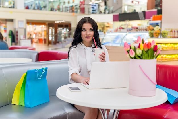 Piękna kobieta odpoczywa po zakupach w kawiarni