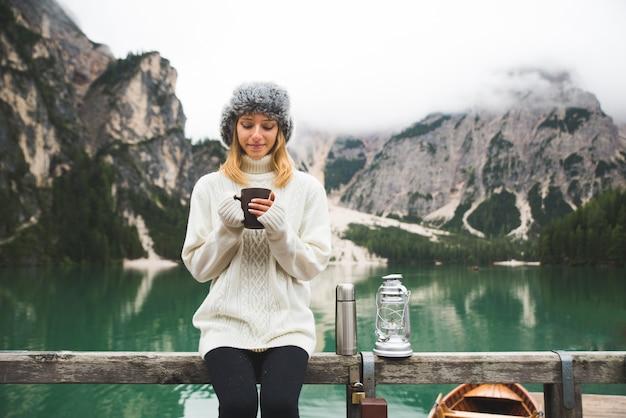 Piękna kobieta odwiedza alpejskie jezioro w braies we włoszech
