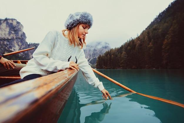 Piękna kobieta odwiedzająca alpejskie jezioro w braies, włochy - turysta w stroju do wędrówek, bawiący się na wakacjach podczas jesiennych liści - pojęcia dotyczące podróży, stylu życia i wędrówki