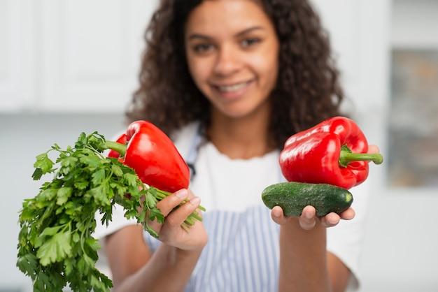 Piękna kobieta oferuje pyszne warzywa