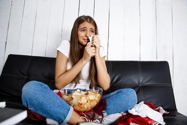 Piękna kobieta ogląda melodramat, płacze, siedzi na kanapie w domu.