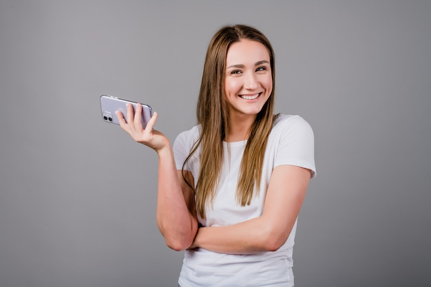 Piękna kobieta ono uśmiecha się z telefonem w ręce odizolowywającej na szarość