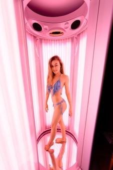 Piękna kobieta opalając się w solarium.