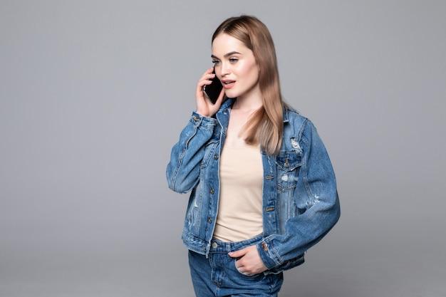 Piękna kobieta opowiada na telefonie komórkowym na szarej ścianie